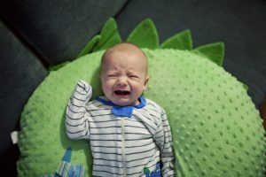 baby crying on a green pillow